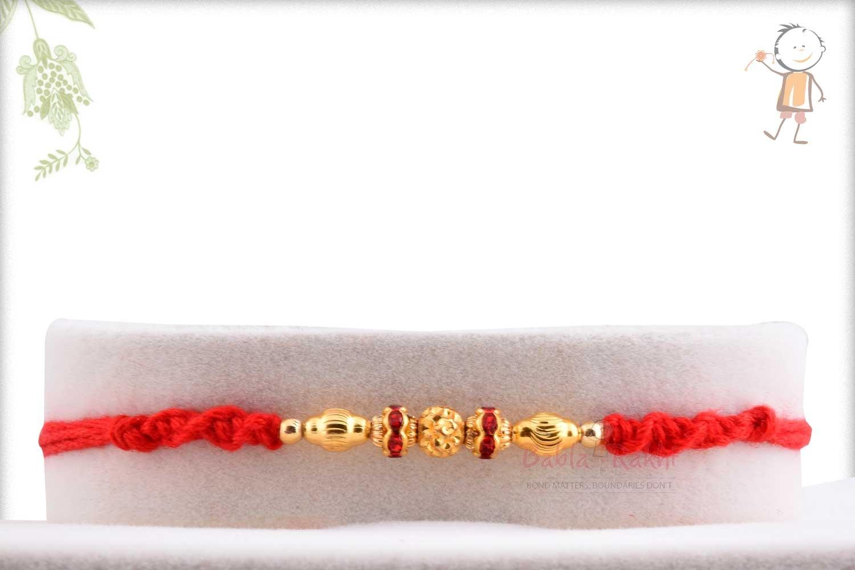 Golden Beads Rakhi with Red Diamond Rings 1