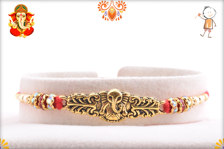 Exclusive Golden Ganesha With Red Tread Rakhi 1